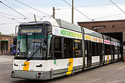 A modern De Lijn electric tram leaves the depot in Ghent, Belgium. The trams have been modernized to use less electricity and become more sustainable public transport.