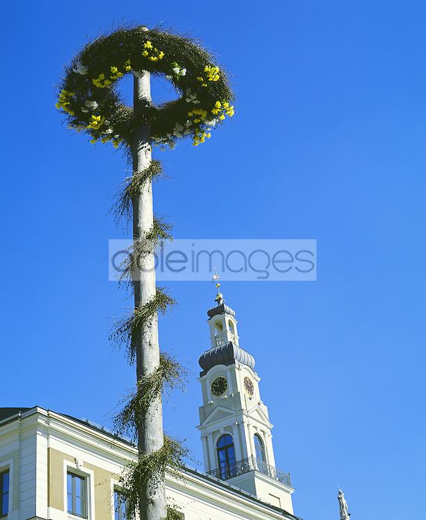 Maypole in riga Latvia with clock tower and blue sky