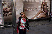 A young woman awaits a bus in front of a large ad billboard for the Body fragrance Burberry Group plc, a British luxury fashion house, manufacturing clothing, fragrance, and fashion accessories. Rosie Alice Huntington-Whiteley (born 18 April 1987) is an English model and actress unveiled as the face of Burberry's newest fragrance, Burberry Body, in July 2011 but also best known for her work for Victoria's Secret, Burberry, and her role as Carly Spencer in the 2011 film Transformers: Dark of the Moon, part of the Transformers film series