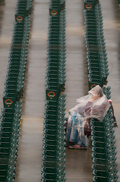 (SPORTS) Lakewood 4/13/2004  Cathie Plaisted of Batavia NY sits in the stands of GPU park with rain poncho on as yet another Blueclaw game is delayed by rain.   Michael J. Treola Staff Photographer....MJT