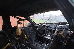 Vandalised and burnt out car in an inner city street,