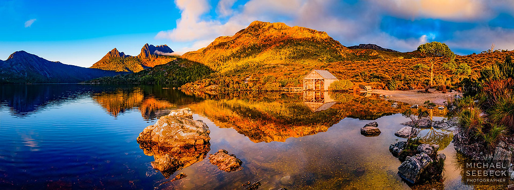 A panoramic photograph of Dove Lake and Cradle Mountain, captured in Autumn, at sunrise. Deciduous beech trees are the orange-coloured trees visible on the upper slopes.<br /> <br /> Limited Edition Print; Edition of 125<br /> <br /> 'Image Size' below refers to the size of the thumbnail. This is a high resolution large format print.