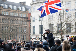 © Licensed to London News Pictures. 06/12/2020. Manchester, UK. Paul Boys, organiser of Rise Up protest in Manchester, speaks to the crowd beneath a Union Jack flag, holding his mic up for the responding cheers in Piccadilly Gardens. Photo credit: Kerry Elsworth/LNP