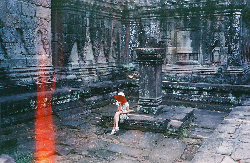 1. When was this photo taken?<br /> <br /> 2004<br /> <br /> 2. Where was this photo taken?<br /> <br /> Cambodia<br /> <br /> 3. Who took this photo?<br /> <br /> I did<br /> <br /> 4. What are we looking at here?<br /> <br /> My daughter Nina is sitting in a temple fanning herself as it was very hot.<br /> <br /> 5. How does this old photo make you feel?<br /> <br /> Very nostalgic. I miss the days when my children were young and together we discovered new places, new cultures.<br /> <br /> 6. Is this what you expected to see?<br /> <br /> I had no idea what was on this roll but expected that it would be from around this time because we soon were using digital cameras<br /> <br /> 7. What kind of memories does this photo bring back?<br /> <br /> Memories of bonding with my family, feelings of possibilities<br /> <br /> 8. How do you think others will respond to this photo?<br /> <br /> I think they will like the red fan and wonder what the child's expression is behind it.