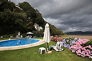"""Portmeirion, in North Wales, is a resort, where no one has ever lived. A self-taught Welsh architect named Sir Clough Williams-Ellis built it out of architectural salvage between the 1920s and 1970s, loosely based on his memories of trips to Portofino. Including a pagoda-shaped Chinoiserie gazebo, some Gothic obelisks, eucalyptus groves, a crenellated castle, a Mediterranean bell tower, a Jacobean town hall, and an Art Deco cylindrical watchtower. He kept improving Portmeirion until his death in 1978, age 94. It faces an estuary where at low tide one can walk across the sands and look out to sea. At high tide, the sea is lapping onto the shores. Every building in the village is either a shop, restaurant, hotel or self-catering accomodation. The village is booked out at high season, with numerous wedding receptions at the weekends. Very popular amongst the English and Welsh holidaymakers. Many who return to the same abode season after season. Hundreds of tourists visit every day, walking around the ornamental gardens, cobblestone paths, and shopping, eating ice-creams, or walking along the woodland and coastal paths, amongst a colourful assortment of hydrangea, rhododendrons, tree ferns and redwoods. The resort boasts two high class hotels, a la carte menus, a swimming pool, a lifesize concrete boat, topiary, pools and wishing wells. The creator describes the resort as """"a home for fallen buildings,"""" and its ragged skyline and playful narrow passageways which were meant to provide """"more fun for more people."""" It does just that.///The swimming pool with flowering hydrangeas. and the village behind on the hill. the estuary is on the right hand side"""