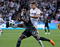 VANCOUVER, April 14, 2018  Vancouver Whitecaps' Alphonso Davies (Front) vies with Los Angeles FC's Dejan Jakovic during the Major League Soccer (MLS) regular season soccer match between Vancouver Whitecaps and Los Angeles FC in Vancouver, Canada, April 13, 2018. Whitecaps won 2-0. (Credit Image: © Andrew Soong/Xinhua via ZUMA Wire)