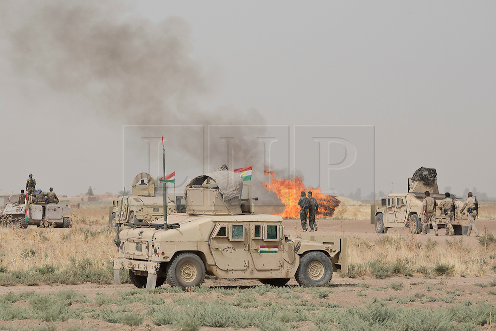 © Licensed to London News Pictures. 11/09/2015. Kirkuk, Iraq. Kurdish peshmerga humvees are seen near a burning haystack during an offensive by the peshmerga to expand a safety zone around Kirkuk, Iraq.<br /> <br /> The offensive, which went unchallenged after ISIS left the area ahead of the attack, saw the peshmerga capture 15 villages along the Kirkuk front line. The objective of the offensive was to expand the safety zone around Kirkuk, stopping militants from firing missiles and rockets in to the city of Kirkuk. 3 peshmerga were killed and 24 wounded due to improvised explosive devices left behind by the militants. Photo credit: Matt Cetti-Roberts/LNP