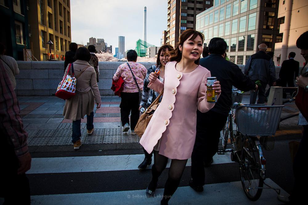 TOKYO, JAPAN, 9 APRIL - Nakameguro - A young woman run to see the cherry blossom with a beer in the hand. She wear a pink coat, the same color as the flowers - april 2012 [FR] Une jeune femme cours pour traverser la rue et voir les cerisiers en fleurs de la riviere Meguro. Elle porte une veste rose identique au couleur des sakura
