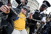 Chains are removed from the wheelchair blockade.  Members of DPAC and UKUncut march from Leicester Square to Trafalgar Square where they block the junction with the Strand. They are protesting about the cuts to Remploy Factories and the Welfare Reform Bill in general. London UK.