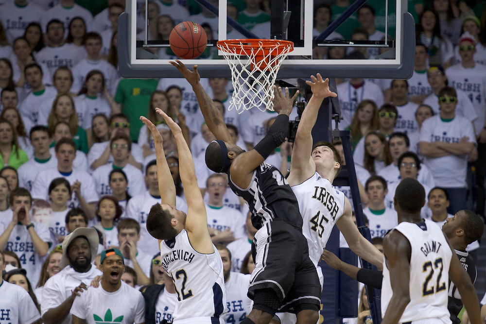 Providence forward LaDontae Henton (#23) goes up for a shot as Notre Dame forward Jack Cooley (#45) and guard Alex Dragicevich (#12) defend in second half action of NCAA Men's basketball game between Providence and Notre Dame.  The Notre Dame Fighting Irish defeated the Providence Friars 75-69 in game at Purcell Pavilion at the Joyce Center in South Bend, Indiana.
