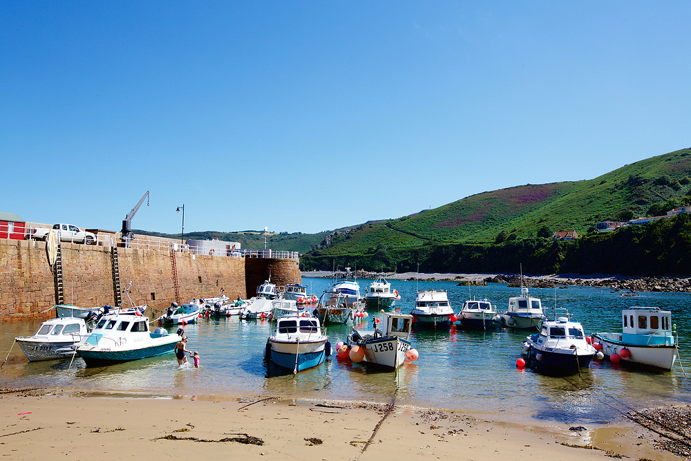 Fishing Boats moored up next to the pier at Bonne Nuit Bay and harbour on a sunny summer day in Jersey, Channel Islands