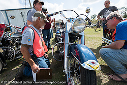 The AMCA Sunshine Chapter Swap Meet during AMCA judge Ken Harvey (seated L) with chief judge Don Dzurick and Laura Tinker Fritz as they scrutinize a great looking Harley-Davidson Panhead at the AMCA (Antique Motorcycle Club of America) Sunshine Chapter National Meet in New Smyrna Beach during Daytona Beach Bike Week. FL. USA. Saturday March 11, 2017. Photography ©2017 Michael Lichter.