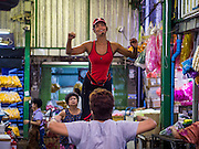 25 AUGUST 2016 - BANGKOK, THAILAND: The instructor leads an aerobics class in Pak Khlong Talat, better known as the Bangkok Flower Market. Public exercise classes are common throughout Thailand and a part of Thailand's public health program. Most of the participants in the exercise class in the Bangkok flower market are older adults, although the class is open to everyone.       PHOTO BY JACK KURTZ