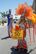 """A woman carries a """"Happy 30th Anniversary: sign while a man on stilts in an Uncle Sam costume looks on."""
