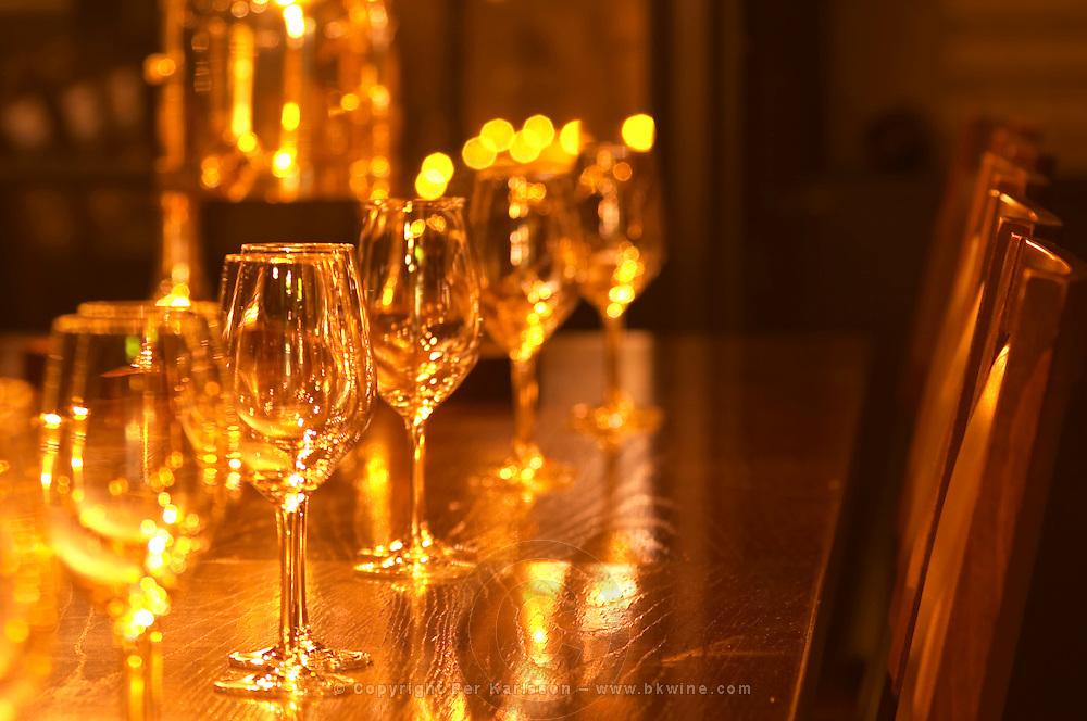 In a wine tasting room glasses lined up on a dark wooden table for a tasting with chairs. in golden light Ulriksdal Ulriksdals Wärdshus Värdshus Wardshus Vardshus Restaurant, Stockholm, Sweden, Sverige, Europe