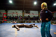 Skeleton wrestler on floor with child in mask in foreground. Lucha Libre wrestling origniated in Mexico, but is popular in other latin Amercian countries, including in La Paz / El Alto, Bolivia. Male and female fighters participate in the theatrical staged fights to an adoring crowd of locals and foreigners alike.
