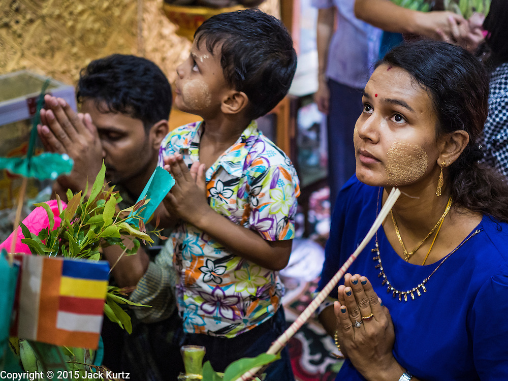 28 OCTOBER 2015 - YANGON, MYANMAR: A woman prays during observances of Thadingyut at Botataung Pagoda in Yangon. Botataung Pagoda was first built by the Mon, a Burmese ethnic minority, around the same time as was Shwedagon Pagoda, over 2500 years ago. The Thadingyut Festival, the Lighting Festival of Myanmar, is held on the full moon day of the Burmese Lunar month of Thadingyut. As a custom, it is held at the end of the Buddhist lent (Vassa). The Thadingyut festival is the celebration to welcome the Buddha's descent from heaven.    PHOTO BY JACK KURTZ