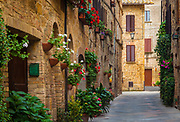"""Pienza, a town and comune in the province of Siena, in the Val d'Orcia in Tuscany (central Italy), between the towns of Montepulciano and Montalcino, is the """"touchstone of Renaissance urbanism."""" In 1996, UNESCO declared the town a World Heritage Site, and in 2004 the entire valley, the Val d'Orcia, was included on the list of UNESCO's World Cultural Landscapes.Pienza was rebuilt from a village called Corsignano, which was the birthplace (1405) of Aeneas Silvius Piccolomini, a Renaissance humanist born into an exiled Sienese family, who later became Pope Pius II. Once he became Pope, Piccolomini had the entire village rebuilt as an ideal Renaissance town. Intended as a retreat from Rome, it represents the first application of humanist urban planning concepts, creating an impetus for planning that was adopted in other Italian towns and cities and eventually spread to other European centers. The rebuilding was done by Florentine architect Bernardo Gambarelli (known as Bernardo Rossellino) who may have worked with the humanist and architect Leon Battista Alberti, though there are no documents to prove it for sure. Alberti was in the employ of the Papal Curia at the time and served as an advisor to Pius. Construction started about 1459. Pope Pius II consecrated the Duomo on August 29, 1462, during his long summer visit. He included a detailed description of the structures in his Commentaries, written during the last two years of his life."""