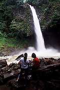 Tourists looking at a waterfall near La Fortuna, in the Arenal Volcano area
