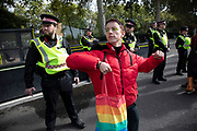 Extinction Rebellion climate change activist dances suggestively in front of a line of police as sites around Westminster are blocked on 8th October 2019 in London, England, United Kingdom. Extinction Rebellion is a climate group started in 2018 and has gained a huge following of people committed to peaceful protests. These protests are highlighting that the government is not doing enough to avoid catastrophic climate change and to demand the government take radical action to save the planet.