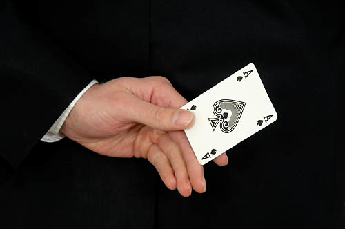 close up of a hand behind the back holding an ace of spades<br />