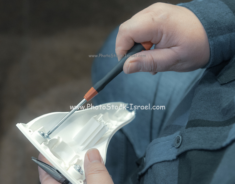 Hands of an Technician holding a screwdriver as he fixes an electronics device