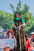 Reaching the Sacred stones a giant human (in all forms of dress) version of their hour glass logo is created - The Extinction Rebellion protest march around the site, led by their Iconic pink boat, Tell the Truth - The 2019 Glastonbury Festival, Worthy Farm. Glastonbury, 27 June 2019