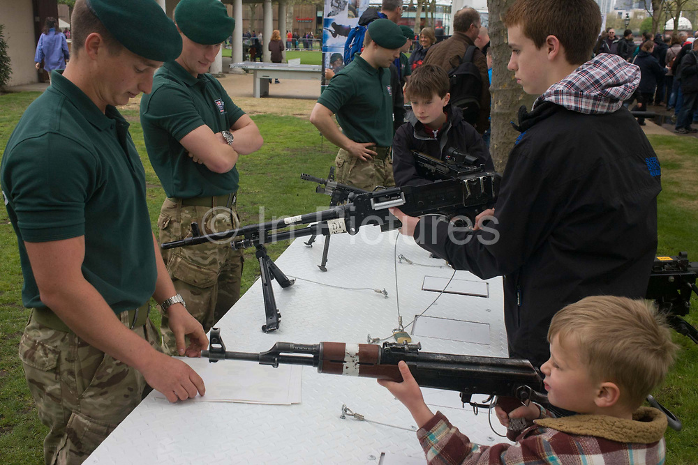 Members of Royal Marines Commandos demonstrate various weaponry to small children and young adults  during a public open-day in Greenwich, London during which the Royal Navy's aircraft carrier HMS Illustrious docked on the river Thames, allowing the tax-paying public to tour its decks before its decommisioning. Navy personnel helped with the PR event over the May weekend, historically the home of Britain's naval fleet.