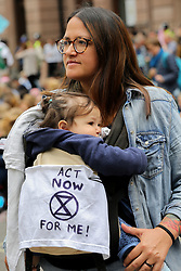 © Licensed to London News Pictures. 15/07/2019. London, UK. 12 months old Juliette and hundreds of Extinction Rebellion climate change activists protest outside the Royal Courts of Justice demanding the legal system take responsibility in the climate change crisis, and ensure the safety of future generations by making ecocide law. The environmental group is staging similar protests in Leeds, Cardiff, Glasgow, Bristol, Norwich and other cities around the country. <br /> <br /> **Permission granted by the parent***.<br /> <br /> Photo credit: Dinendra Haria/LNP