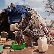 """Kenya, camp de réfugiés de Dadaab - Dagahaley. Mumina, 30 ans, 6 enfants, de Jilib. Mumina est arrivée en décembre 2010. Ces dernières semaines, le UNHCR a entâmé une opération de déplacement des réfugiés vers des zones qui ne risquent pas l'inondation. Mumina refuse de quitter l'endroit où elle a établi son abri. Elle n'ira pas au nouveau camp  Ifo II, ou alors le plus tard possible. Son fils est en convalescence, il ne supporterait pas le trajet. Le petit soulève son t-shirt pour découvrir une protubérance rose vif à l'abdomen. """"Il vient de se faire opérer à Nairobi d'une malformation de naissance"""", explique sa maman encore inquiète."""