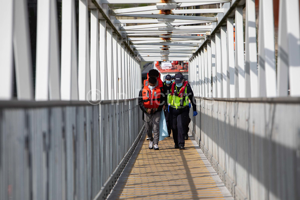 Asylum seekers arriving into Dover up the dock walkway ramp accompanied by Boarder Force officers after being on board a Boarder Force RIB boat, they were rescued in the English Channel while crossing in small inflatable dinghy on the 31st of March 2021 in Dover, Kent, United Kingdom. About 30 men and women arrived today on two small boats they were taken off the boat by UK Boarder Force and taken into a processing centre on the dock side.