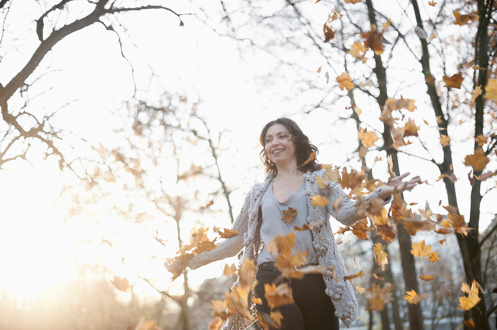 Mature woman throwing autumn dry leaves in air in the park, Bavaria, Germany