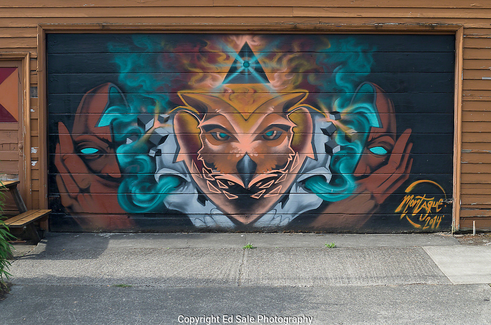 A colorful mural painted on a garage door in N.E. Portland, Oregon shows the head of an other-worldly creature with the heads of two men on other side