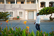 A man talks on his mobile telephone whilst another exercises on the seafront at dawn, Pondicherry, India<br /> Pondicherry now Puducherry is a Union Territory of India and was a French territory until 1954 legally on 16 August 1962. The French Quarter of the town retains a strong French influence in terms of architecture and culture.