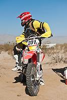 201x motorcycle rider Derek Duncan leaves Honda pit #2 at race mile 70, 2012 San Felipe Baja 250, San Felipe, Baja California, Mexico.