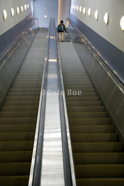 one person going up a very long escalator