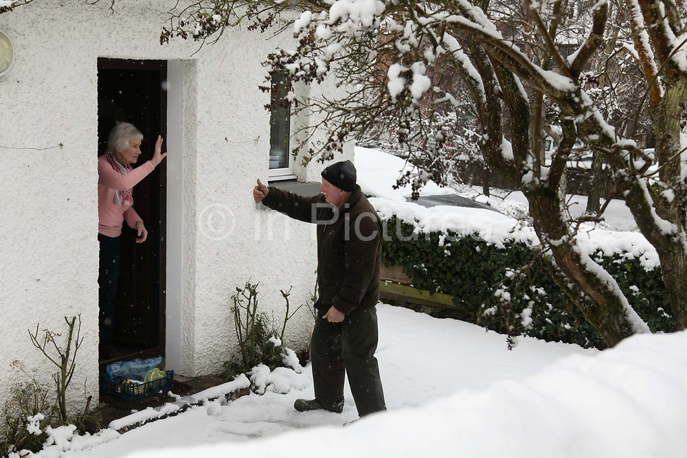 Gordon Anderson delivers fresh milk and vegetables to a local resident shielding from the snow on 14th of January 2021 in Stow, Scottish Borders, United Kingdom. Gordon Anderson runs a fresh milk and vegetables delivery service with his wife and they deliver to local houses and farms in and around the village of Stow. The first real snow of the year has been falling all night and morning and the village is covered in fresh snow.