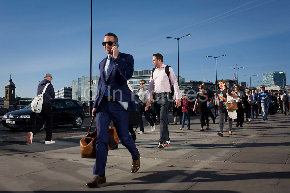 Londoners cross southbound over London Bridge during the evening rush hour. A young man strides along with a handset to his ear, followed by others walking away from the City of London. There has been a crossing over the Thames here since the Romans first forded the river in the early 1st Century with subsequent medieval and Victorian stone bridges becoming an important thoroughfare from the City on the north bank, to Southwark on the south where transport hubs such as the mainline station gets commuters to the suburbs and satellite towns.