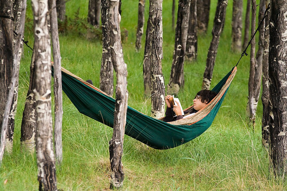Austin Silva, a highschool biology intern at the Valles Caldera National Preserve, New Mexico, reads in his hammock, strung up in a forest, on his day off.