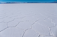 Salar de Uyuni is the world's largest salt flat at 10,582 square kilometers (4,086 sq mi). It is located in the Daniel Campos Province in Potosí in southwest Bolivia, near the crest of the Andes and is at an altitude of 3,656 meters (11,995 ft) above sea level.<br /> <br /> The Salar was formed as a result of transformations between several prehistoric lakes. It is covered by a few meters of salt crust, which has an extraordinary flatness with the average altitude variations within one meter over the entire area of the Salar. The crust serves as a source of salt and covers a pool of brine, which is exceptionally rich in lithium. It contains 50 to 70% of the world's lithium reserves, which is in the process of being extracted. The large area, clear skies, and exceptional flatness of the surface make the Salar an ideal object for calibrating the altimeters of Earth observation satellites.