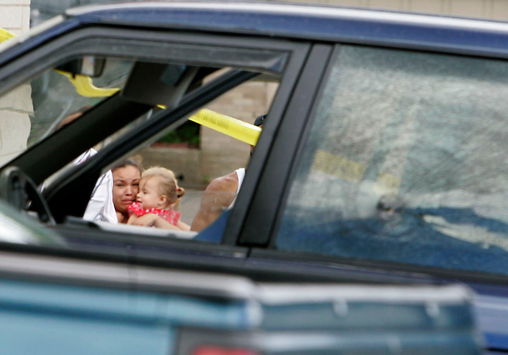 Waterbury, Conn. 18 June 2005: An unidentified woman holds a child on Cooke Street as she looks into the window of the van in which 34-year-old Antonio Santos was shot and killed on Saturday afternoon in a convenience store parking lot...Josalee Thrift Photo