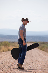 cowboy with a guitar case on a dirt road in the desert