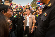 26 JANUARY 2014 - BANGKOK, THAILAND: Thai police escort elections workers away from the polling place at Bang Kapi School after protestors shut the site down. Anti-government protestors forced the closure of polling places in Bangkok Sunday as a part of Shutdown Bangkok. Early voting was supposed to be Sunday January 26 but blocked polling places left hundreds of thousands of people unable to vote casting the February 2 general election into doubt and further gridlocking Thai politics. Protestors blocked access to gates and entry ways to polling places and election officials chose the close them rather than confront protestors. Shutdown Bangkok has been going for 12 days with no resolution in sight. Suthep, the leader of the anti-government protests and the People's Democratic Reform Committee (PDRC), the umbrella organization of the protests,  is still demanding the caretaker government of Prime Minister Yingluck Shinawatra resign, the PM says she won't resign and intends to go ahead with the election.    PHOTO BY JACK KURTZ