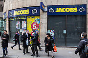 London city workers walk past a Jacobs camera shop that has recently closed down near Bank, London, United Kingdom.  Jacobs Photo Digital, a family-run British business, went into administration in June 2012.  The retail business was established in 1939, but has been a victim of the economic slowdown as there has been a shift in purchasing toward internet-based retailers.