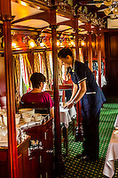Waitress serving breakfast in the pillared pre-1940s dining car on the luxury Rovos Rail train between Pretoria and Cape Town, South Africa.