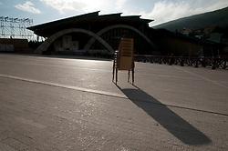 """È stata inaugurata il 1° luglio 2004, la nuova Chiesa di San Pio da Pietrelcina progettata dall'architetto Renzo Piano. Esattamente 45 anni prima, nel 1959,  veniva inaugurata la chiesa """"grande"""" di Santa Maria delle Grazie. .Sorta a fianco del santuario e convento in cui visse il frate, ha la forma di una conchiglia e la sua pianta ricorda quella della spriale archimedea. Enormi archi parto dal perimetro esterno e terminano nel fulcro della """"conchiglia"""" dove è posto l'altare. Possenti staffe d'acciaio, ancorate agli archi, sorreggono la volta che ricoperta di rame preossidato espone alla vista un intenso un colore verde-rame.   .Con i suoi 6000 mq, è la seconda chiesa più grande in Italia per dimensioni, dopo il Duomo di Milano. Può ospitare oltre 7000 persone e per la sua realizzazione sono state impiegati 30.000 metri cubi di calcestruzzo, 1.320 blocchi in pietra di Apricena, 70.000 metri cubi di scavo in roccia, 60.000 chili di acciaio, 500 mq di vetro, 19.500 mq di rame preossidato. Ogni anno è meta di oltre sei milioni di pellegrini..Nella foto il piazzale antistane la chiesa (sullo sfono). In primo priano una pila di sedie utilizzate per i posti a sedere sul pioazzale stesso in occasione dei grandi eventi."""
