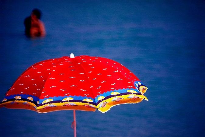 A couple kiss in the ocean, with a big beach umbrella in the foreground