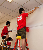 Up With People cast members Ryotaro Tsukii from Japan and Tomohiro Hayashi from Japan apply a fresh coat of paint to the dining room walls in the Congregational Church on Wednesday morning.  (Karen Bobotas/for the Laconia Daily Sun)