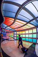 "An airline pilot walks through the tunnel, passing ""Sky's the Limit"" by artist Michael Hayden at O'Hare International Airport, Chicago, Illinois USA."