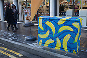 Brightly painted with bananas design, a telecoms junction box in Southwark in South London. These boxes have started to appear all over the borough as unique street art.